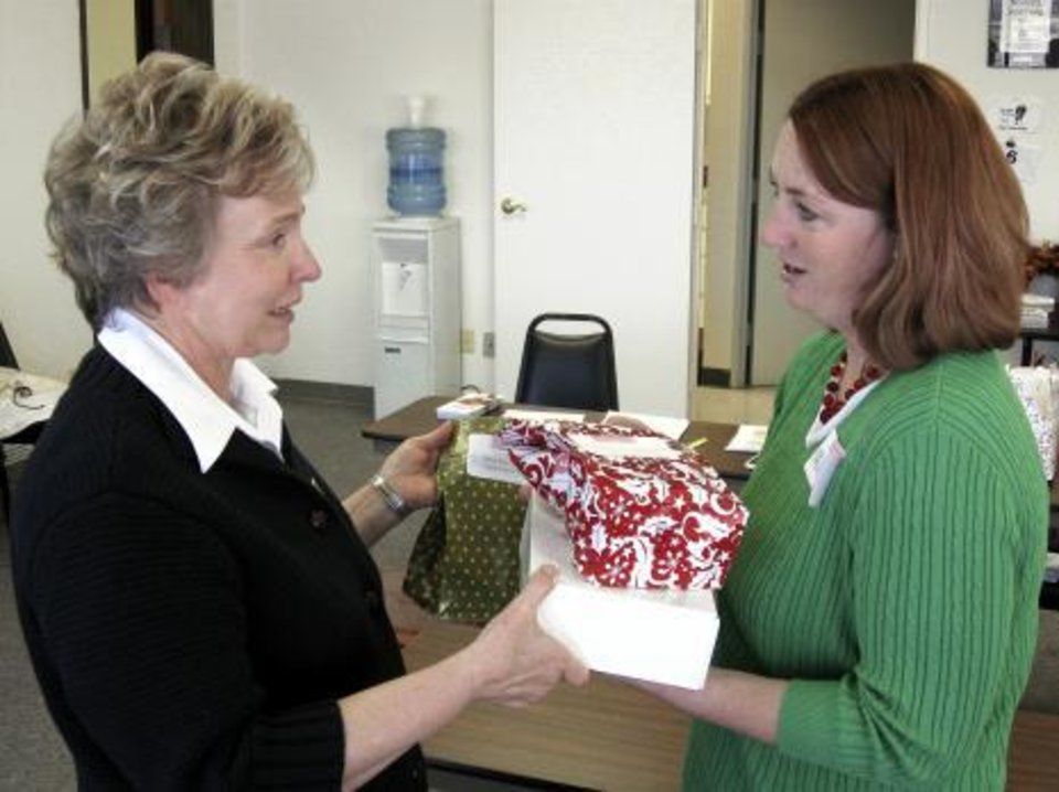 Photo -  Lida Clinton, left, gets her order of baked goods from Michelle Sutherlin on Monday at the United Way of Norman. Sutherllin and a group of her friends formed Confections for a Cause, which raised more than $2,000 for the United Way by spending hundreds of hours baking cookies, pies and cakes. PHOTOS BY JAMES S. TYREE, THE OKLAHOMAN