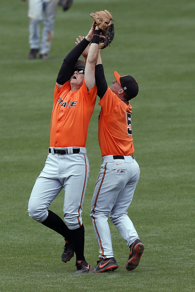 Oklahoma State's Craig McConaugh,left,   collides with Donnie Walton after making a catch during the Bedlam baseball game between the University of Oklahoma and Oklahoma State University at the Chickasaw Bricktown Ballpark in Oklahoma CIty, Sunday, May 12, 2013. Photo by Sarah Phipps, The Oklahoman