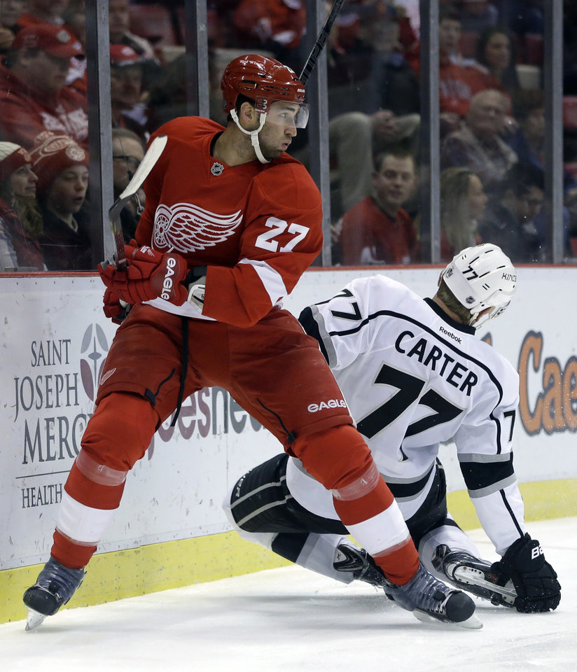 Photo - Los Angeles Kings center Jeff Carter (77) is checked by Detroit Red Wings defenseman Kyle Quincey (27) during the first period of an NHL hockey game in Detroit, Saturday, Jan. 18, 2014. (AP Photo/Carlos Osorio)
