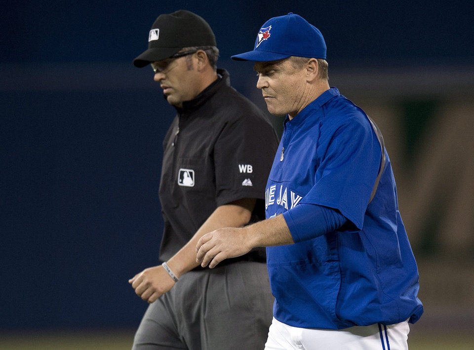 Photo - Toronto Blue Jays manager John Gibbons and second base umpire Manny Gonzalez, left, walk off the field after the Jays had a triple play turned on them by the St. Louis Cardinals during the sixth inning of a baseball game in Toronto on Friday, June 6, 2014. (AP Photo/The Canadian Press, Frank Gunn)