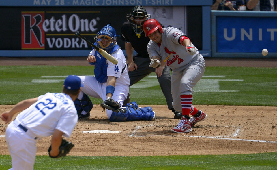 St. Louis Cardinals' Yadier Molina, right, loses his bat as Los Angeles Dodgers starting pitcher Clayton Kershaw, left,  pitches and catcher A.J. Ellis catches during the third inning of their baseball game, Sunday, May 26, 2013, in Los Angeles.  (AP Photo/Mark J. Terrill)