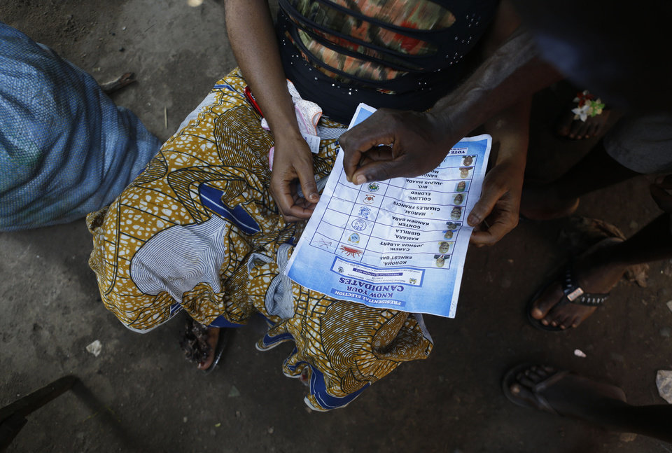 A ruling party supporter from the Mabella slum uses a sample ballot paper to show neighborhood women how to cast a valid vote for incumbent President Ernest Bai Koroma, in Freetown, Sierra Leone Friday, Nov. 16, 2012. Ten years after the end of a devastating civil war, Sierra Leone will go to the polls on Saturday to choose between candidates including incumbent President Koroma and opposition leader Julius Maada Bio. (AP Photo/Rebecca Blackwell)