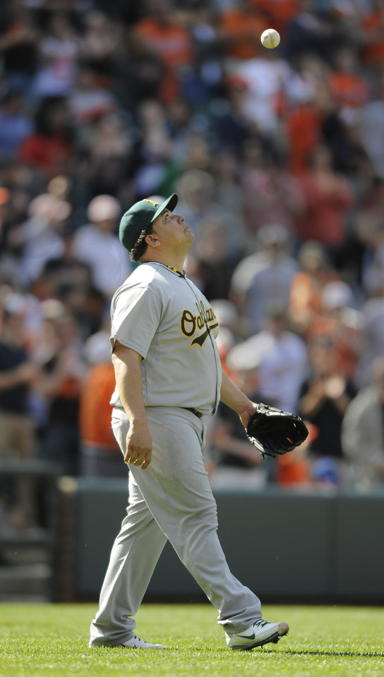 Photo -   FILE - In this April 29, 2012, file photo, Oakland Athletics pitcher Bartolo Colon tosses the ball in the air after committing a throwing error during the ninth inning of a baseball game against the Baltimore Orioles in Baltimore. Colon, a former AL Cy Young Award winner, has been suspended for 50 games by Major League Baseball on Wednesday, Aug. 22, 2012, after testing positive for testosterone. (AP Photo/Gail Burton, File)