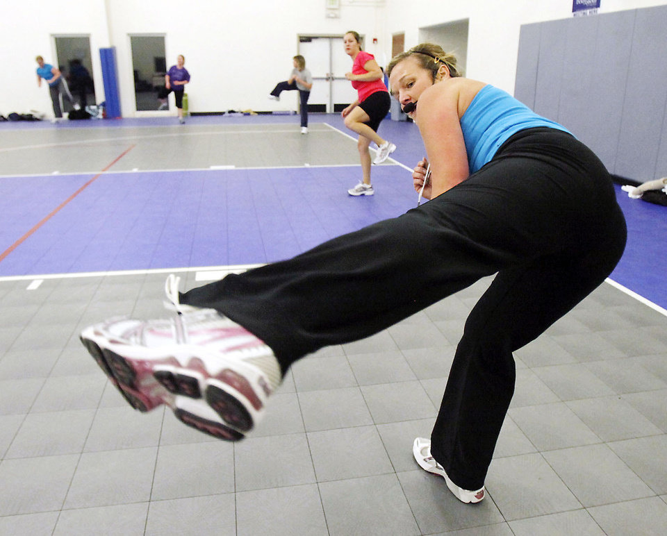 Photo - Instructor Kerri Collison leads exercises during a New Year's Day Boot Camp at Holy Trinity Lutheran Church in Edmond. The boot camp is at 7 a.m. every Saturday in January. PHOTOS BY PAUL HELLSTERN, THE OKLAHOMAN