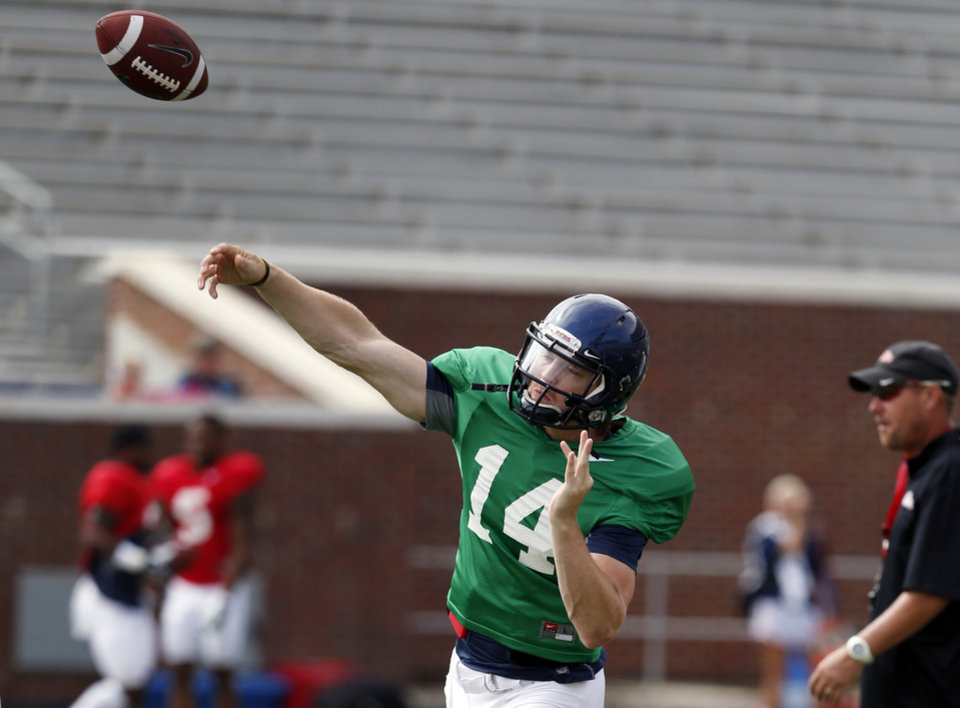 Photo - Mississippi quarterback Bo Wallace (14) passes as football coach Hugh Freeze walks past during their final open NCAA college football practice, Saturday, Aug. 9, 2014, at Mississippi, in Oxford, Miss. Players were involved in individual and team drills. (AP Photo/Rogelio V. Solis)