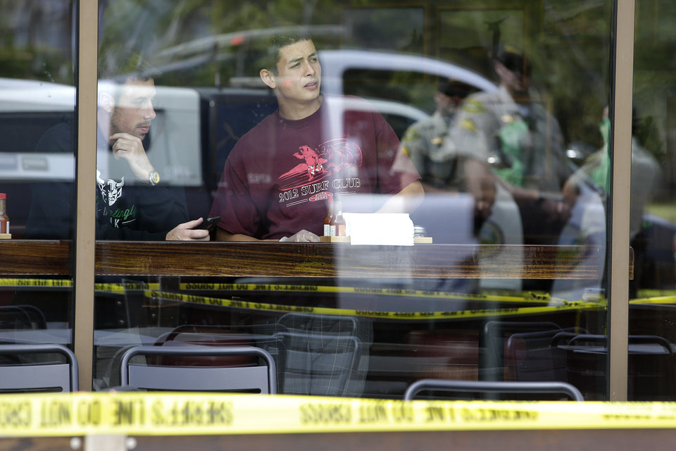Photo - Two men watch from a restaurant near the scene of a shooting on Saturday, May 24, 2014, in Isla Vista, Calif. A drive-by shooter went on a rampage near a Santa Barbara university campus that left seven people dead, including the attacker, and others wounded, authorities said Saturday. (AP Photo/Jae C. Hong)