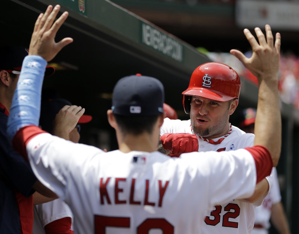Photo - St. Louis Cardinals' Matt Adams, right, is congratulated by teammate Joe Kelly after hitting a two-run home run during the second inning of a baseball game against the Washington Nationals, Sunday, June 15, 2014, in St. Louis. (AP Photo/Jeff Roberson)