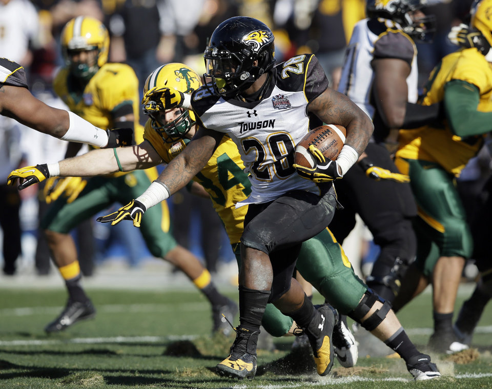 Photo - Towson running back Terrance West (28) looks for a gap at the line of scrimmage on a running play in the first half of the FCS championship NCAA college football game against North Dakota State, Saturday, Jan. 4, 2014, in Frisco, Texas. (AP Photo/Tony Gutierrez)