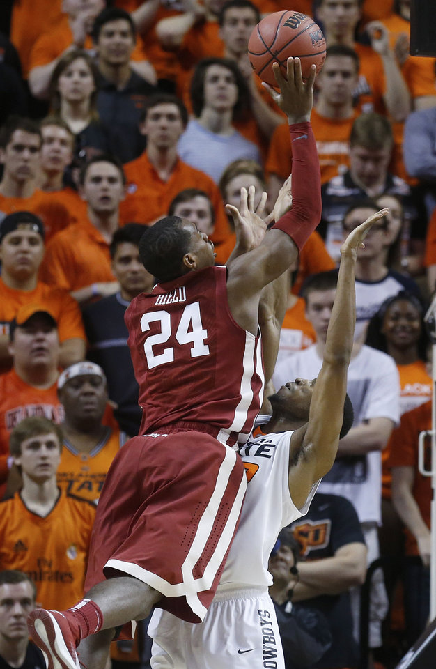 Photo - Oklahoma guard Buddy Hield (24) shoots over Oklahoma State wing Markel Brown (22) in the second half of an NCAA college basketball game in Stillwater, Okla., Saturday, Feb. 15, 2014. Oklahoma won 77-74. (AP Photo/Sue Ogrocki)