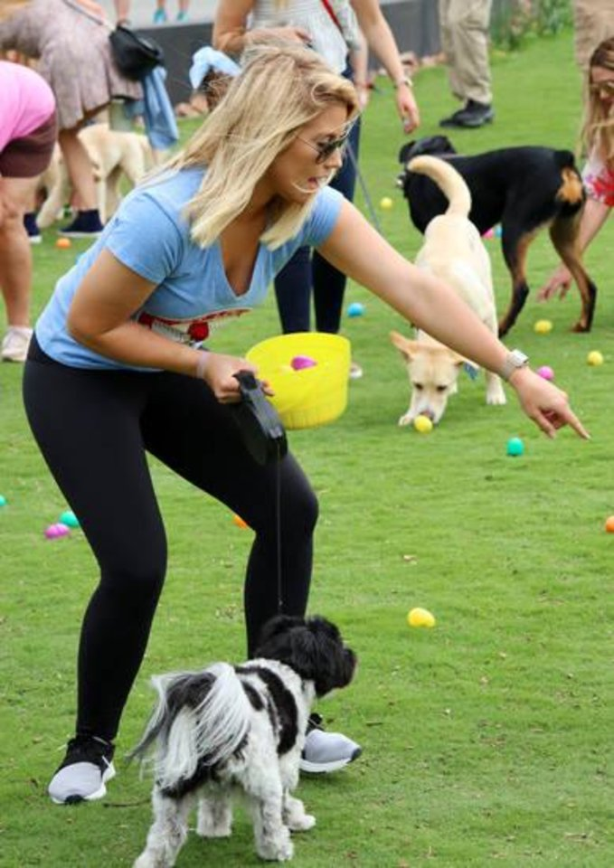 Photo -  Rashell Conrady, of Edmond, directs her dog Chooch toward an egg during the Easter egg hunt at Myriad Botanical Gardens. [PHOTO BY DOUG HOKE, THE OKLAHOMAN]