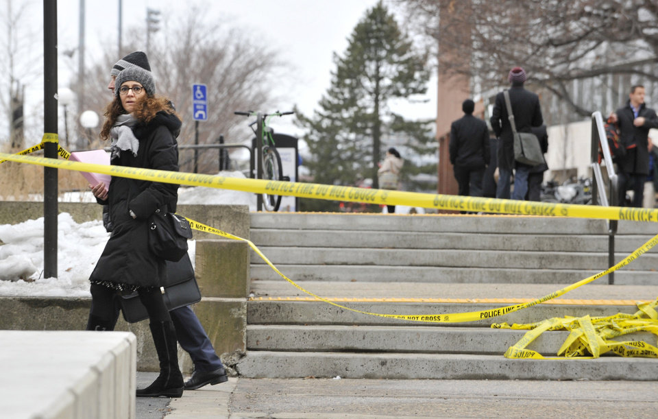 Pedestrians walk by police tape on the MIT Campus in Cambridge, Mass.,after police responded to reports of a gunman on campus that Cambridge police later said were unfounded, Saturday, Feb. 23, 2013. Police said that officers searched for a man reported to be carrying a long rifle and wearing body armor and found nothing. A spokeswoman for the university says the school also called off a campus-wide lockdown. (AP Photo/Josh Reynolds)