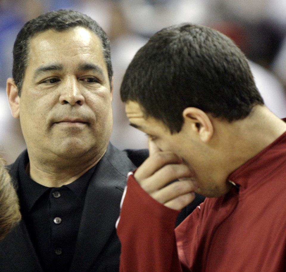 Photo - Former Oklahoma head coach Kelvin Sampson, left, looks on as his son Kellen wipes his eye during Senior Night festivities before the men's college basketball game between the University of Oklahoma and the University of Kansas at the Lloyd Noble Center in Norman, Okla., Monday, Feb. 26, 2007. By Matt Strasen, The Oklahoman ORG XMIT: KOD