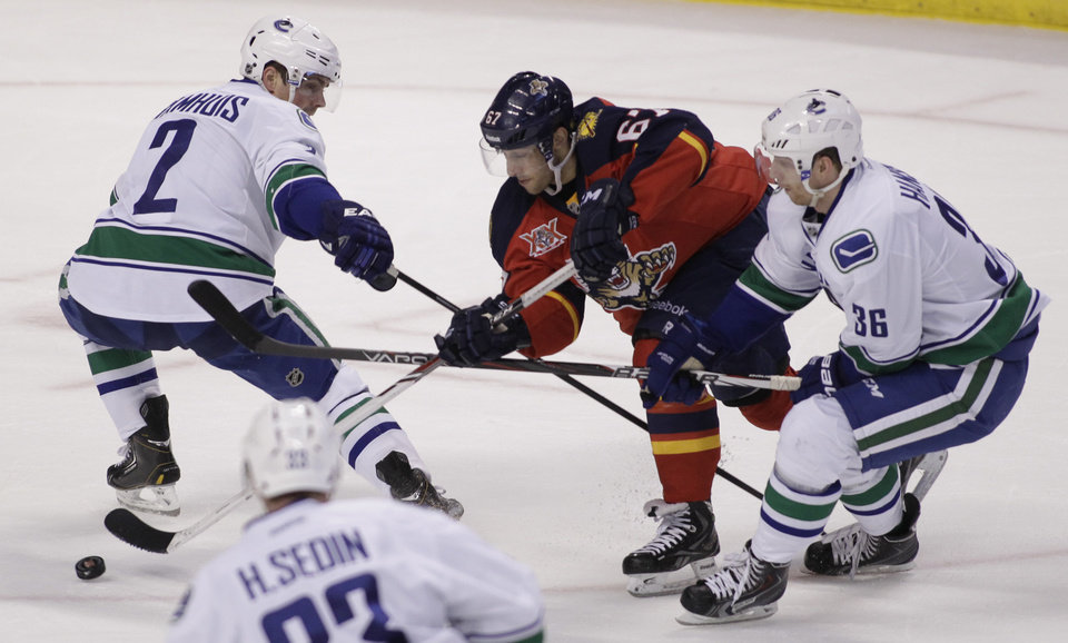 Photo - Florida Panthers' Vincent Trocheck, center, moves the puck as Vancouver Canucks' Dan Hamhuis (2) and Jannik Hansen (36), of Denmark, defend during the first period of an NHL hockey game on Sunday, March 16, 2014, in Sunrise, Fla. (AP Photo/Luis M. Alvarez)