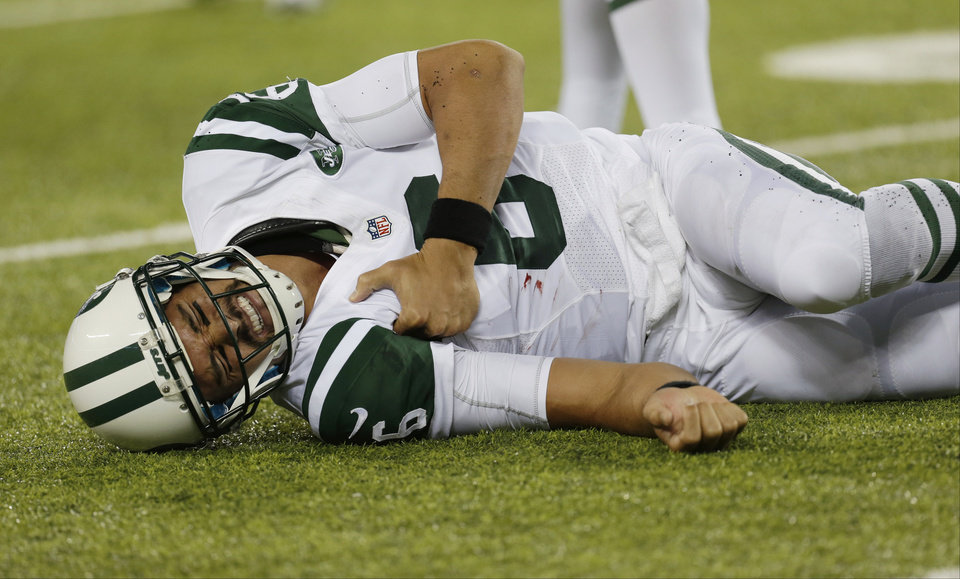 Photo - New York Jets quarterback Mark Sanchez (6) reacts to an injury during the second half of a preseason NFL football game against the New York Giants, Saturday, Aug. 24, 2013, in East Rutherford, N.J. He left the game with what appeared to be a shoulder injury. (AP Photo/Julio Cortez)