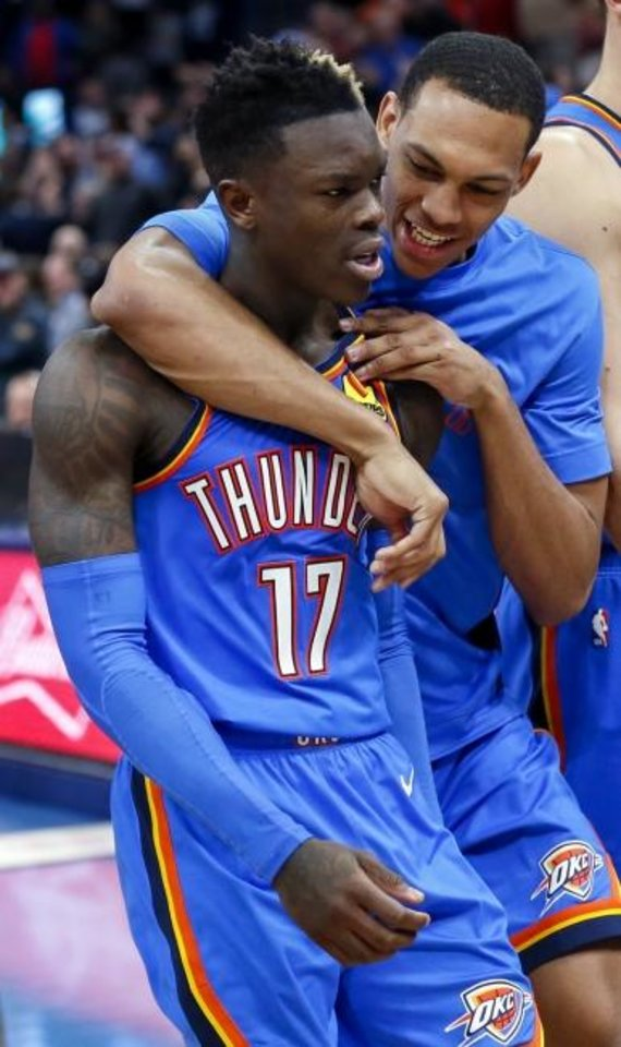 Photo -  Oklahoma City's Dennis Schroder, front, gets a hug from Darius Bazley while walking back to the bench. [Nate Billings/The Oklahoman]