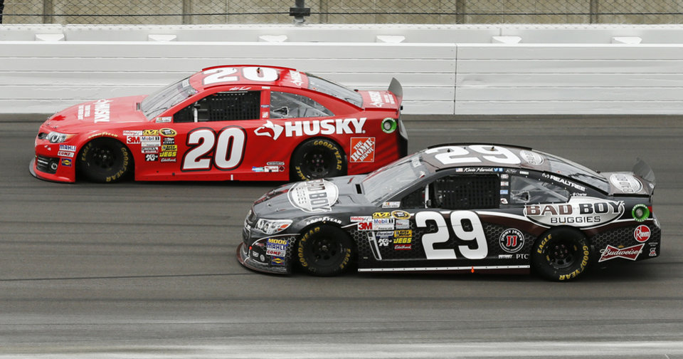 Photo - Driver Matt Kenseth (20) holds off Kevin Harvick (29) during a NASCAR Sprint Cup series race at Kansas Speedway in Kansas City, Kan., Sunday, April 21, 2013. (AP Photo/Orlin Wagner)