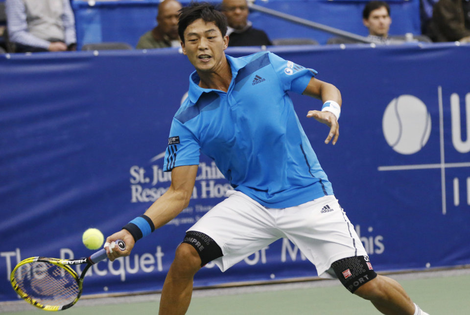 Photo - Lu Yen-hsun, of Taiwan, hits a return to Ivo Karlovic, of Croatia, in the semifinals of the U.S. National Indoor Tennis Championships on Saturday, Feb. 15, 2014, in Memphis, Tenn. Lu retired due to injury after losing the first set, 6-1. (AP Photo/Rogelio V. Solis)