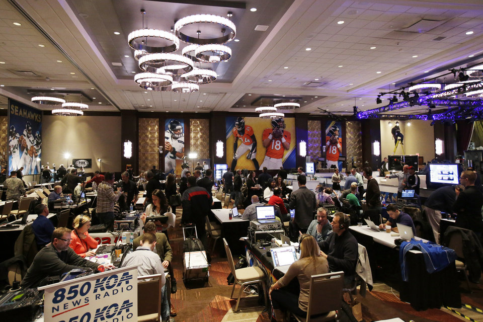 Photo - Broadcasters work on radio row at the NFL Super Bowl XLVIII media center, Monday, Jan. 27, 2014, in New York. The NFL's championship game between the Denver Broncos and Seattle Seahawks is scheduled for Sunday, Feb. 2 in East Rutherford, N.J. (AP Photo/Matt Slocum)