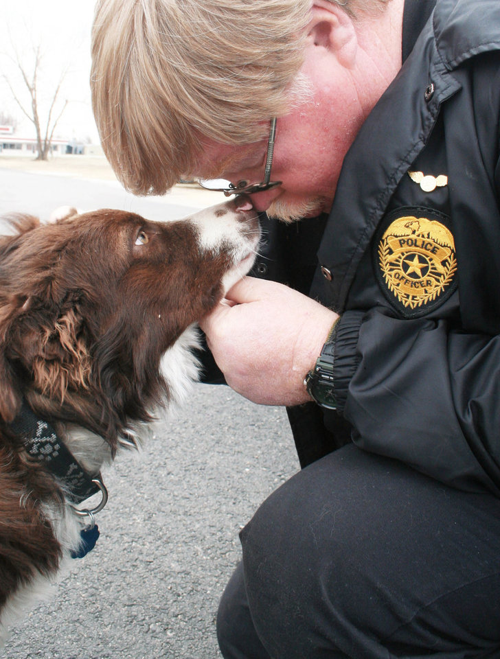 Photo - Webbers Falls Police Chief Tim Brown bonds with the town's newly adopted dog, Dragnet.  Photo BY SUSAN HYLTON, TULSA WORLD