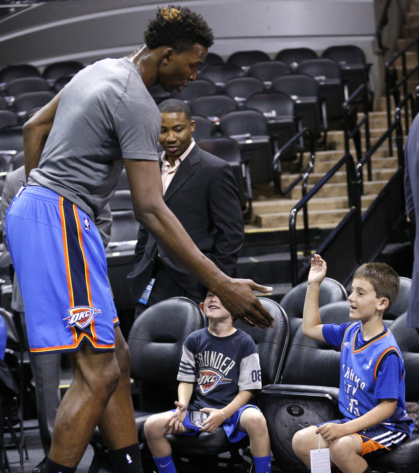 Photo - Oklahoma City's Hasheem Thabeet (34) greets fans Andrew Ismailer, right, and Sam Ismailer of San Francisco before Game 5 of the Western Conference Finals in the NBA playoffs between the Oklahoma City Thunder and the San Antonio Spurs at the AT&T Center in San Antonio, Thursday, May 29, 2014. Photo by Sarah Phipps