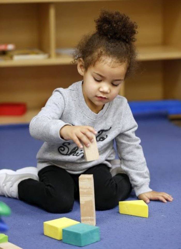 Photo -  Sophie Pughsley, 2, plays with blocks recently at Putnam City Smart Start Childcare. [Nate Billings/The Oklahoman]