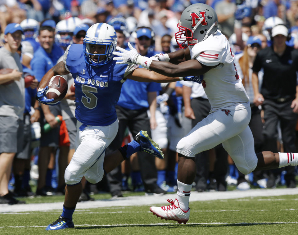 Photo - Air Force running back Devin Rushing, left, runs for a long gain as Nicholls State defensive back B.T. Sanders defends in the second quarter of an NCAA college football game at Air Force Academy, Colo., on Saturday, Aug. 30, 2014. (AP Photo/David Zalubowski)