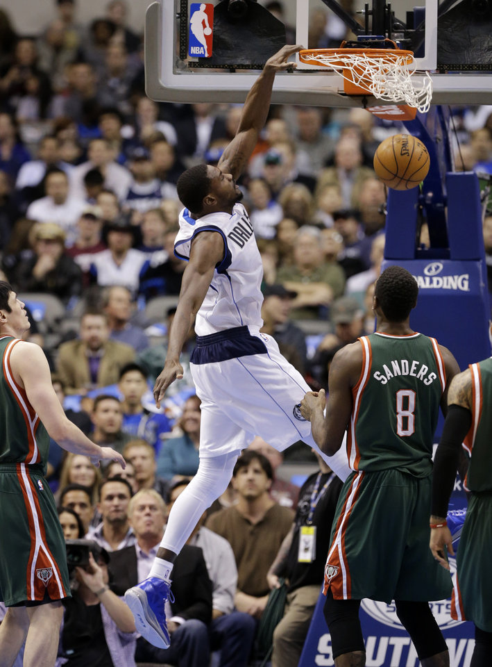Dallas Mavericks' Bernard James, center, dunks as Milwaukee Bucks' Ersan Ilyasova, left, and Larry Sanders (8) watch in the first half of an NBA basketball game Tuesday, Feb. 26, 2013, in Dallas. (AP Photo/Tony Gutierrez)