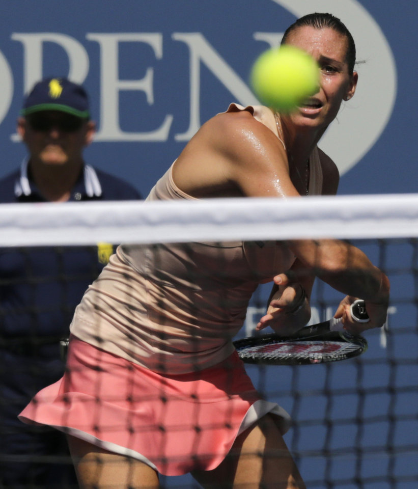 Photo - Flavia Pennetta, of Italy, returns a shot against Casey Dellacqua, of Australia, during the fourth round of the 2014 U.S. Open tennis tournament, Monday, Sept. 1, 2014, in New York. (AP Photo/Charles Krupa)