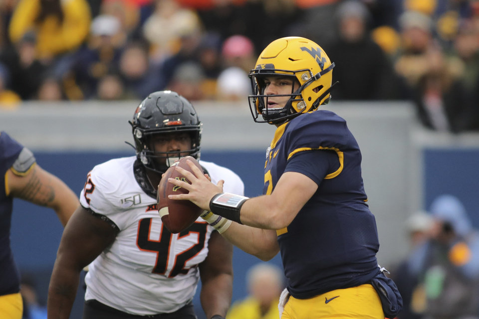 Photo - West Virginia quarterback Jarrett Doege (2) rolls out of the pocket as Oklahoma State's Jayden Jennings (42) pursues during the second quarter of their NCAA college football game  in Morgantown, W.Va., on Saturday, Nov. 23, 2019. [AP Photo/Chris Jackson]