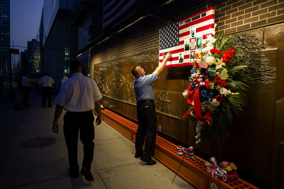 Photo - FDNY Firefighter Mike Bellantoni of New York prepares a memento at the Firefighter's Memorial adjacent to the World Trade Center Wednesday, Sept. 11, 2013 before the start of the official ceremonies at the 9/11 Memorial nearby. (AP Photo/Craig Ruttle)