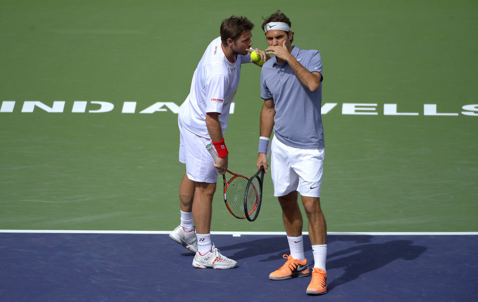 Photo - Roger Federer, of Switzerland, right, and doubles partner Stanislas Wawrinka, of Switzerland, talk during a match at the BNP Paribas Open tennis tournament against Rohan Bopanna, of India, and Aisam-Ul-Haq Qureshi, of Pakistan,  Friday, March 7, 2014 in Indian Wells, Calif. (AP Photo/Mark J. Terrill)
