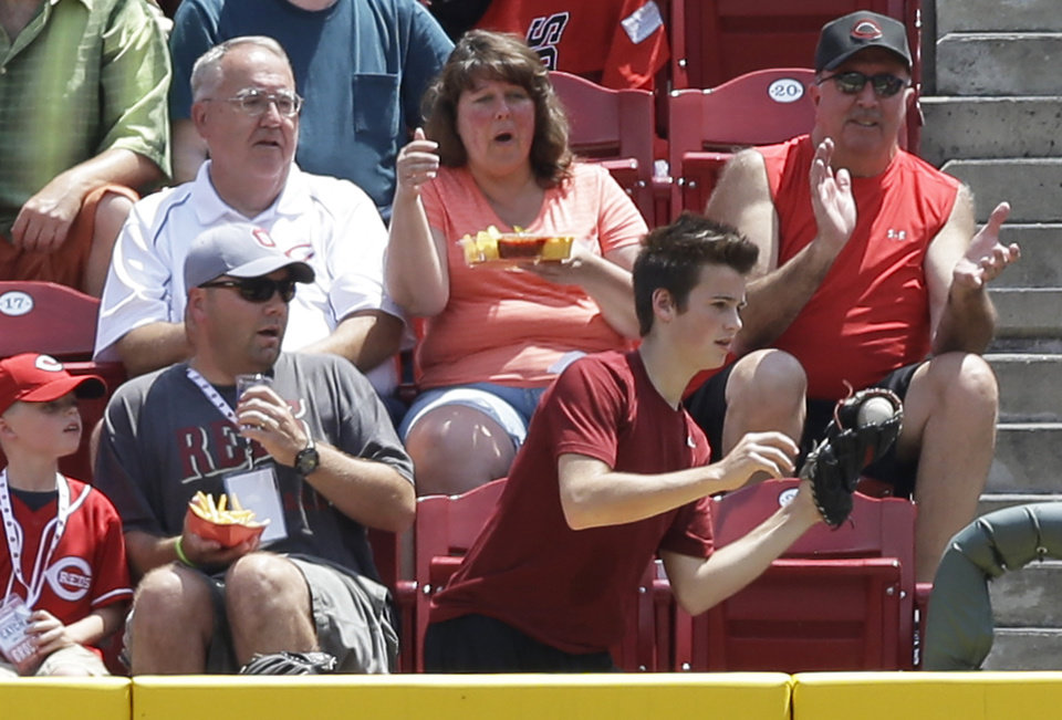 Photo - A young fan catches a two-run home run hit by Cincinnati Reds' Todd Frazier off Toronto Blue Jays starting pitcher R.A. Dickey in the fifth inning of a baseball game, Sunday, June 22, 2014, in Cincinnati. (AP Photo/Al Behrman)