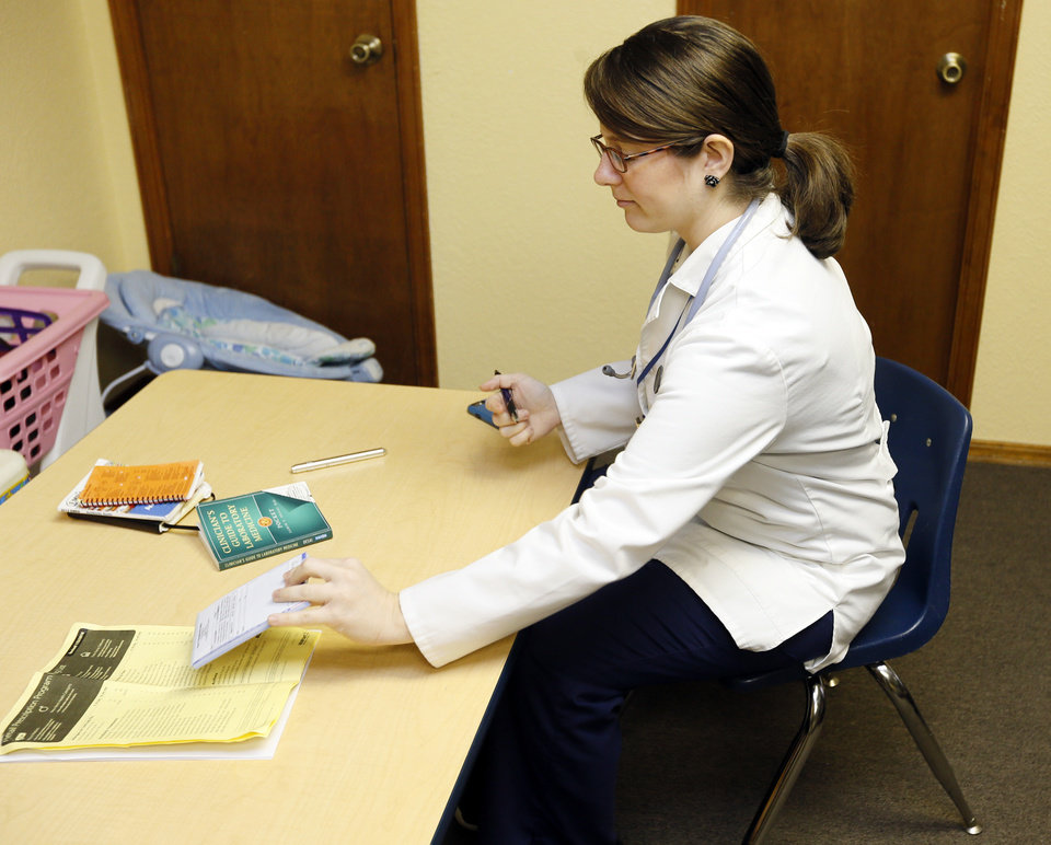 Photo -  Physician assistant Brenda Kelley, of Norman, prepares to see patients during the Hope Medical Clinic at the Slaughterville Baptist Church. [PHOTO BY NATE BILLINGS, THE OKLAHOMAN]