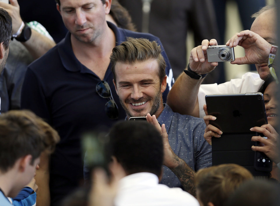 Photo - Former English soccer player David Beckham takes pictures as he arrives to attend  the World Cup final soccer match between Germany and Argentina at the Maracana Stadium in Rio de Janeiro, Brazil, Sunday, July 13, 2014. (AP Photo/Hassan Ammar)