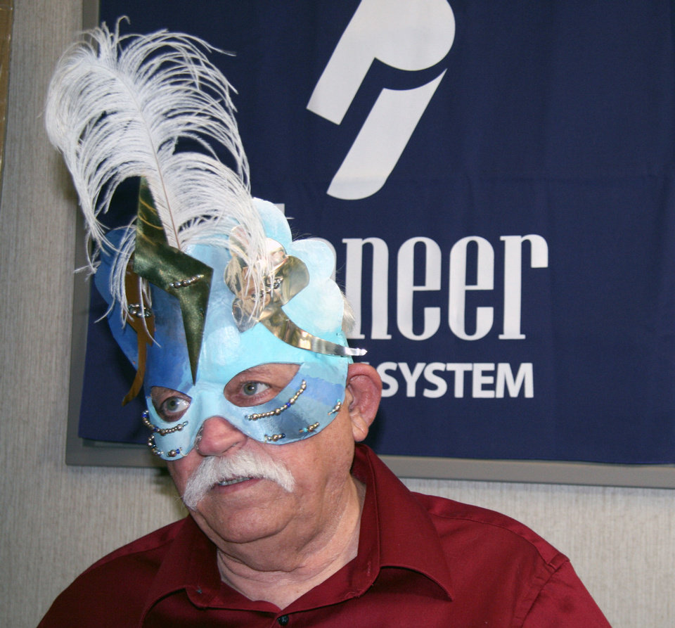 Photo - Patrick Riley wears a mask he constructed at a presentation at the Norman Public Library last year. PHOTO PROVIDED