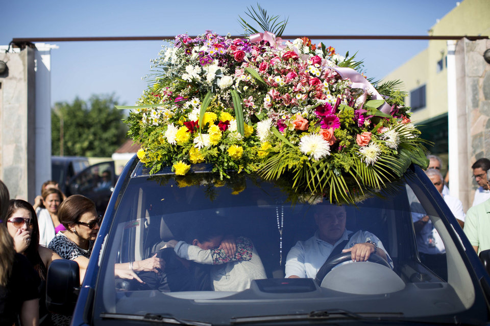 Photo - Relatives of Genesis Carmona, embrace inside the hearse carrying her body during her funeral, Friday, Feb. 21, 2014 in Valencia, Venezuela. The university student and beauty queen who was slain during a political protest on Feb.18 in Valencia, was buried Friday, a victim of what government opponents say is the kind of indiscriminate violence that has been used to stifle dissent across the country by supporters of President Nicolas Maduro. (AP Photo/Rodrigo Abd)