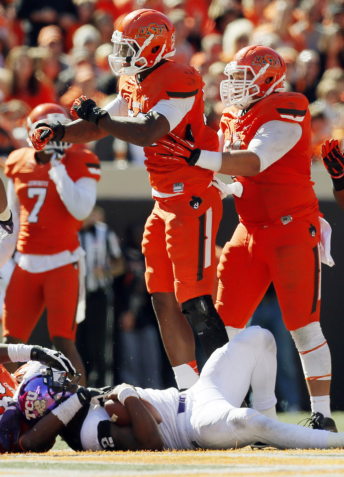 Photo - Oklahoma State's Jimmy Bean (92), middle, celebrates a sack of TCU's Trevone Boykin (2) with teammate James Castleman (91), right, during a college football game between the Oklahoma State University Cowboys (OSU) and the Texas Christian University Horned Frogs (TCU) at Boone Pickens Stadium in Stillwater, Okla., Saturday, Oct. 19, 2013. OSU won, 24-10. Photo by Nate Billings, The Oklahoman