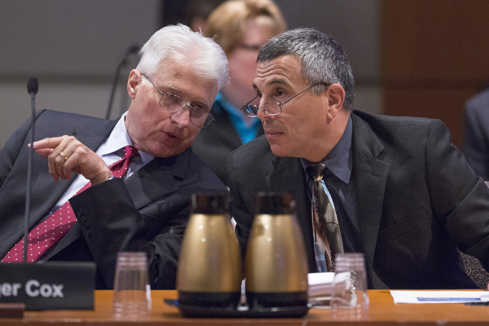 Photo - National Transportation Safety Board (NTSB) lead investigator Bill English, right, talks with investigator Roger Cox during an NTSB hearing in Washington, Tuesday, June 24, 2014, to establish the cause of Asiana Flight 214  airlines crash in San Francisco, and to make safety recommendations. (AP Photo/ Evan Vucci)