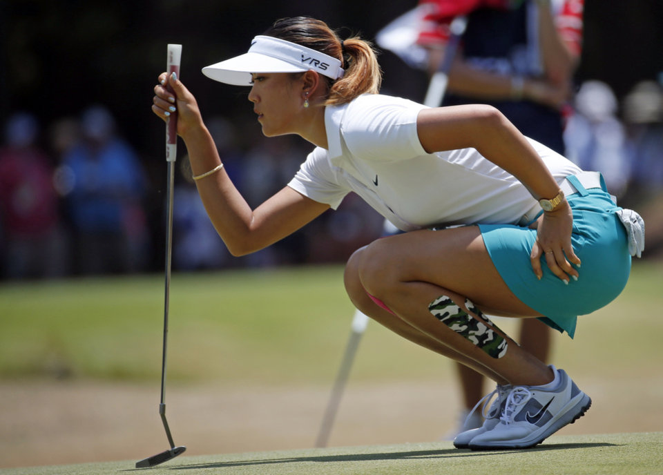 Photo - Michelle Wie lines up a putt on the first green during the first round of the U.S. Women's Open golf tournament in Pinehurst, N.C., Thursday, June 19, 2014. (AP Photo/John Bazemore)