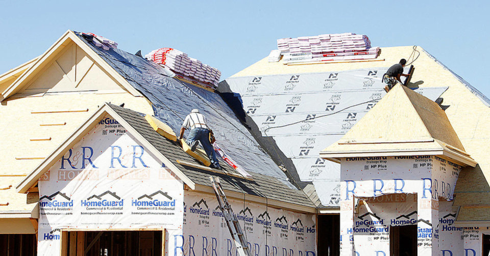 Photo - Roofers work on a house at 14521 S Robinson in Oklahoma City.  PAUL B. SOUTHERLAND - The Oklahoman