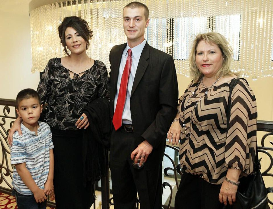 Photo - Chris and Jerrae Wilson, with their son Jackson, 6, and Marla Grant pose for a photo during a reception for
