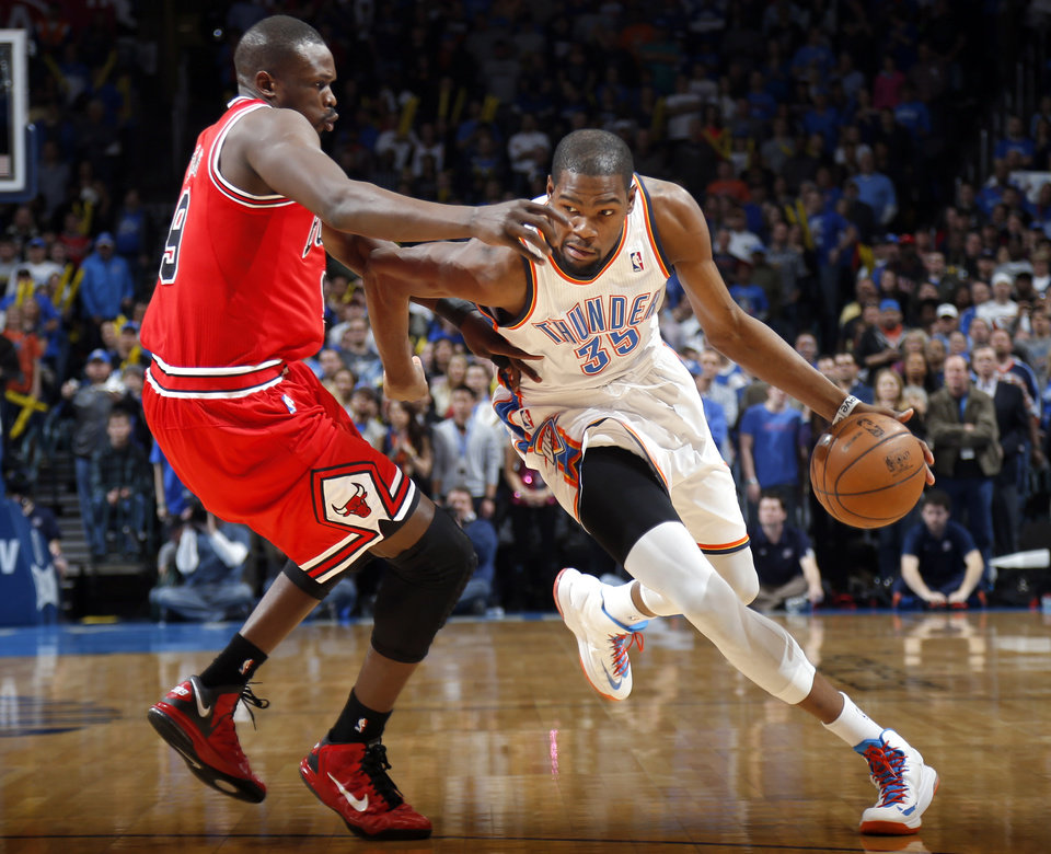 Photo - Oklahoma City's Kevin Durant (35) tries to get past Chicago's Luol Deng (9) during the NBA game between the Oklahoma City Thunder and the Chicago Bulls at Chesapeake Energy Arena in Oklahoma City, Sunday, Feb. 24, 2013. Photo by Sarah Phipps, The Oklahoman