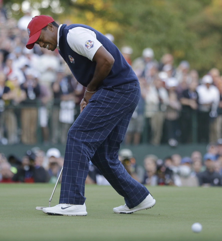 Photo -   USA's Tiger Woods reacts after missing a birdie putt on the 18th hole to lose a four-ball match at the Ryder Cup PGA golf tournament Friday, Sept. 28, 2012, at the Medinah Country Club in Medinah, Ill. (AP Photo/Chris Carlson)
