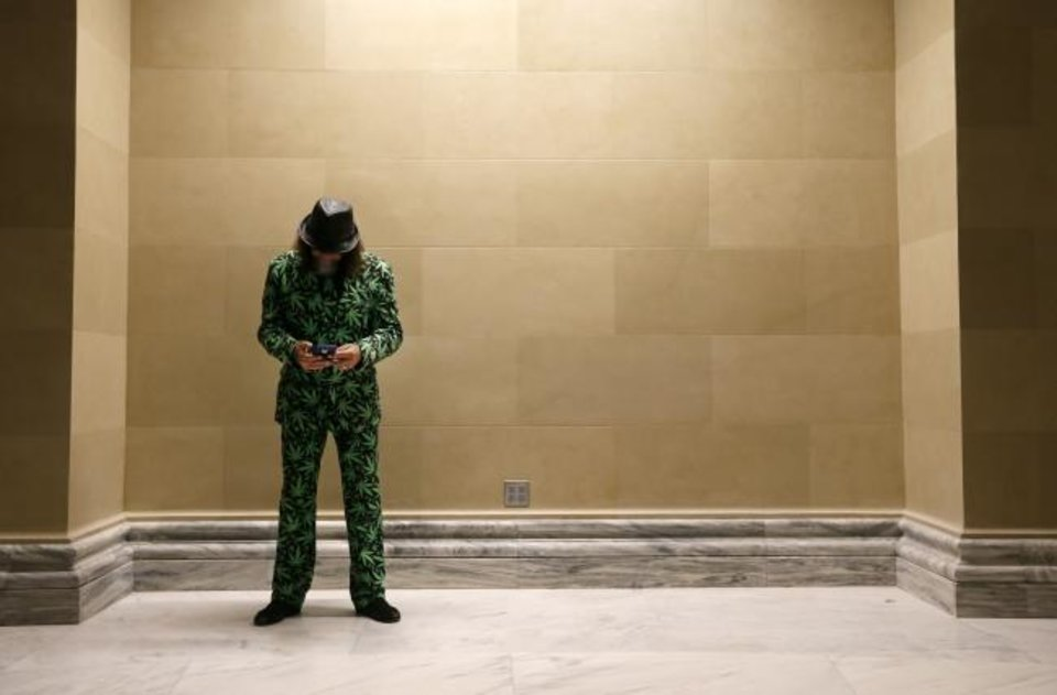 Photo -  Daniel Curriston of Oklahoma City checks his phone during March the Capitol 2020 on the second floor of the state Capitol in Oklahoma City, Thursday, Feb. 6, 2020. The rally was to protest many of the bills filed in the legislative session that would affect medical marijuana patients and businesses. [Nate Billings/The Oklahoman]