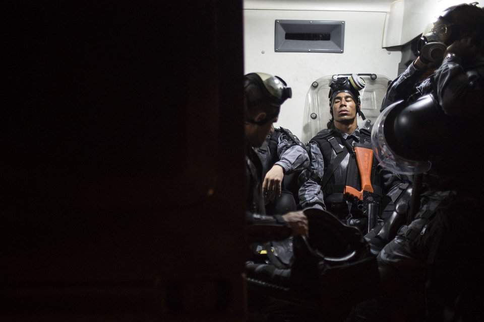 Photo - Riot police get a respite from manning anti-government protests as they rest inside a police vehicle near the Cidade de Deus, or City of God slum in Rio de Janeiro, Brazil, Friday, June 21, 2013. City centers around Brazil were still smoldering on Friday after 1 million protesters took to the streets amid growing calls on social media for a general strike next week. While most protesters were peaceful, some small groups clashed violently with police, who responded in some cases with tear gas, pepper spray and rubber bullets. (AP Photo/Felipe Dana)