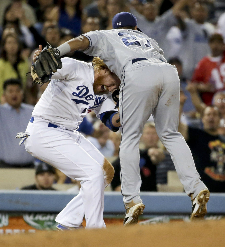 Photo - Los Angeles Dodgers' Justin Turner, left, gets tangled up with San Diego Padres third baseman Yangervis Solarte after an over throw during the fourth inning of a baseball game in Los Angeles, Tuesday, Aug. 19, 2014. (AP Photo/Chris Carlson)