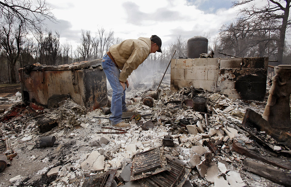 Photo - Kenneth Wertz digs through the remains of his house of more than 40 years as he looks for a few salvageable remains from the house that was destroyed by wildfires on Friday, April 10, 2009, in Choctaw, Okla.  Photo by Chris Landsberger, The Oklahoman