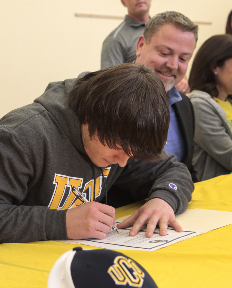 Photo - Eli Hooks signs a letter of intent with UCO, with his dad, Bryan,  during signing day at Deer Creek High School, Wednesday, February 4, 2014. Photo by David McDaniel, The Oklahoman