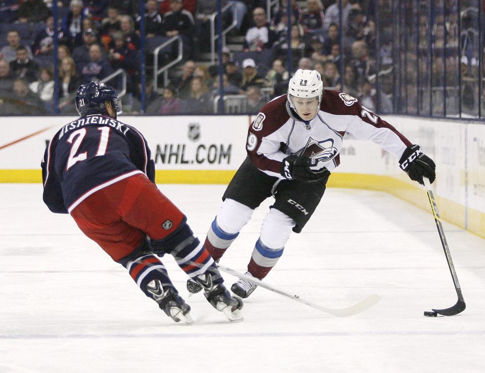 Photo - Columbus Blue Jackets' David Wisniewski (21) tries to slow down Colorado Avalanche's Nathan MacKinnon (29) during the first period of an NHL hockey game, Tuesday, April 1, 2014, in Columbus, Ohio. (AP Photo/Mike Munden)