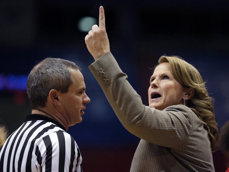 Photo - Kansas head coach Bonnie Henrickson, right, talks with referee Mark Zentz, left, during the second half of an NCAA college basketball game against Oklahoma State in Lawrence, Kan., Wednesday, Jan. 22, 2014. Oklahoma State defeated Kansas 64-56.(AP Photo/Orlin Wagner)